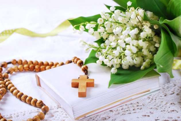 the first holy communion with wooden rosary,prayer  book and bunch of lily of the valley